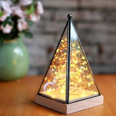 Add a romantic glow to your favorite spaces with this pyramid shaped table top lamp. Inside the metal and glass top a string of glowing fairy lights creates the perfect ambience for special occasions or relaxed evenings at home. <br>  <ul><li> Architectural table top design with dew drop LED lights </li> <li> Removable glass and metal top with a natural beech wood base  </li> <li> Choose a plug with a dimmer switch or remote control  </li> </ul>