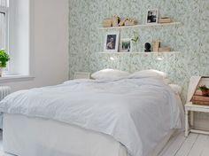 Des étagères au-dessus du lit
