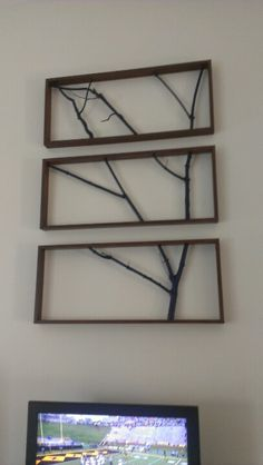 """Wood branches in a frame. From another pin on pinterest with an 8""""x10"""" tidal size. This is 4' by 6 '. You can see or  32"""" tv below.frame was made  from three  1""""x4""""s. Trees spray painted blue."""