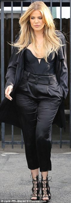 Matrix vibes: The 30-year-old reality stardressed her curvaceous figure in a sleek head-to-toe black ensemble including a lingerie one-piece, high-waisted glossy trousers and long overcoat