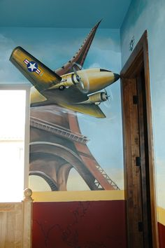 For those that love travel, the Golden Gate bridge in one corner of the room and the Eiffel tower in the other. Real plane parts accessorize the mural. . here one of the wings is real and extends out of the wall and in the other corner, real propellers were added to the wing and move when the air condition hits. Artwork by Carmen Benoit at Carmen Illustrates.