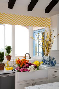 #apron front sink on white cabinets with bold colors accessorizing the place.