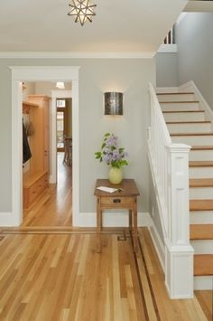 Lovely entry with light grey walls, white trim, medium hardwood