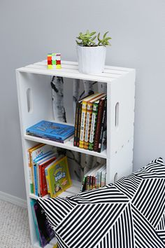 """Abby at 'Sew Much Ado"""" put together this DIY wood crate bookshelf tutorial, and it's awesome. We especially love the birch tree wallpaper she used to back the bookshelves with. (Don't worry, it just sticks on!) Also, she has the cutest little guy on the planet helping her out! Go check out her step by step photos."""