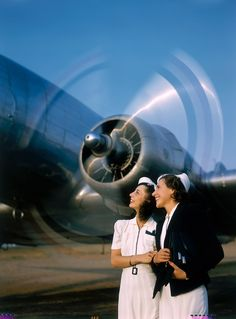 Two young women stand near a turning aircraft propeller, 1940. Photograph by Luis Marden, National Geographic Creative