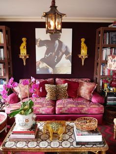 Chinoiserie Chic: foo dogs, an elephant, a pagoda lantern, an orchid, a double gourd lamp, and a gilded faux bamboo coffee table. I love the aubergine walls, pink sofa, and leopard pillow.