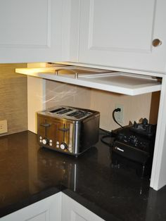 Hide your kitchen appliances with a garage style cabinet door.