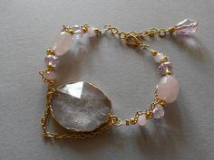 Bracciale con quarzo rosa, cristalli e centrale in agata rosa, montato con catena e componenti in metallo coloro oro. Realizzazione artigianale.