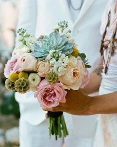 A bouquet of roses, craspedia, and succulents