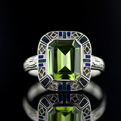 This classic Art Deco ring features a 3.10 carat emerald cut peridot, within a surround of green and blue enamel and a lattice work of 14 karat white gold. @designerwallace