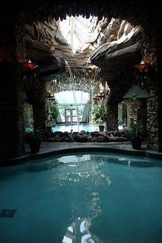 Piscine intérieure avec ouverture au toit sous forme de roche et petites cascades d'eau qui tombent dans une piscine