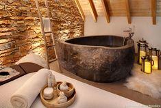 La salle de bains qui va bien avec l'ambiance montagne cosy : baignoire en pierre, mur en pierres, parquet, couleurs naturelles... Chalet de montagne cocooning