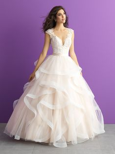 A scalloped illusion V-neckline framed with cap sleeves tops the lace sweetheart bodice of this Allure Bridals Romance 3017 wedding dress. A sleek band cinches the waistline and covered buttons accent the illusion back. Overlapping layers of organza ruffles adorn the ball gown skirt and chapel train. Available in sizes 2-32