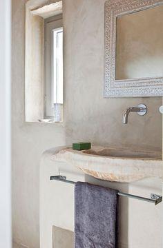 reforma baño casa rural rehabilitada, con lavabo de piedra sobre mueble de obra, grifos empotrados, paredes microcemento.