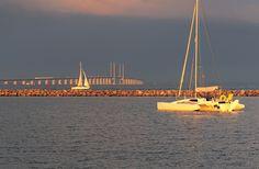 Yachts in the Oresund Strait, near Copenhagen, with the Oresund Bridge to Malmo, Sweden behind.
