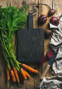 #Garden carrots and beetroots  Healthy food cooking background. Vegetable ingredients. Fresh garden carrots and beetroots on rustic wooden background with dark cutting board in center top view copy space horizontal composition