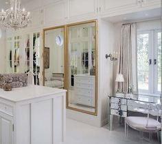 source: Annelle Primos  Stunning master closet with floor to ceiling built-ins boasting glass closets doors alongside gold framed mirror paneled closets across from closet island with white counter illuminated by a white tole chandelier. A mirrored dressing table stands below the French window which is dressed in linen drapes with tape trim paired with an acrylic Klismos Chair below lit by a crystal droplet wall sconce.