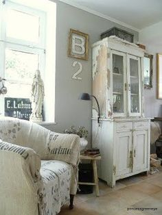 Love the chair with different grain sack fabrics, the statue in the window, the wide windowsill itself, the hutch, the lamp attached to the hutch, the little stool......