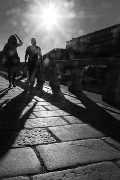 Raining Light - Man, woman and the sun in a black and white picture at sunset.