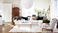 Living room with white furniture and accents in wood, black, and grey Daniella Witte