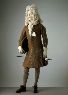 Dress coat  England, Britain (made)  1700-1720 (made)  Wool embroidered with silver gilt thread, lined with silk and interfaced with buckram.The coat, waistcoat and breeches remained the primary ensemble for men's formal and informal dress throughout the 18th century. The muted shade of brown in a fine wool is typical for the date and for English men's dress, as is the silver-gilt embroidery. Up until the 1730s, coats were knee-length, buttoning right to the hem, with full pleats at the…