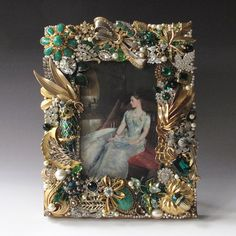 Beautiful handcrafted heirloom quality frame composed of vintage jewelry. Find emerald glass rhinestones, green jade-like stones, gold and silvertone metals, enamel, rhinestones and pearls. A large enameled Jomaz owl brooch is a focal point of this frame as is a rhinestone and emerald cabochon trembler brooch. The frame is made with over 30 pieces of vintage jewelry and is dated and signed by the artist. Made of wood finished with a gold wash, it has a quality easel back. A beautiful and…
