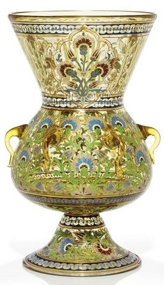 A GILT AND ENAMELLED AMBER GLASS MOSQUE LAMP FRANCE OR AUSTRIA, 19TH CENTURY Of typical form with six applied glass handles, the foot and body decorated with a repeating frieze of blue, grey and red carnations issuing from green vine, the flaring neck with pseudo-calligraphy punctuated with three cusped cartouches with similar floral sprays, later suspension chains attached to handles