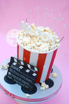 A double barrel popcorn bucket for a little girl celebrating her TV acting debut. The popcorn is real (having once spent all day making it from fondant, I vowed never again). The clapperboard is fondant covered with an edible image and written on in non-toxic chalk.   I put little lights in the cake, so Maddy could see her name in lights. I also added a couple of sparklers for good measure.