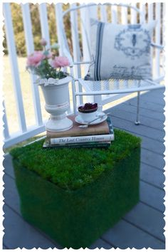 Faux grass covers a plastic crate to create this cute grass covered ottoman for your porch or deck. #diymyspring