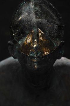 Une Goutte d'Eau de Verre géante en équilibre sur le Visage d'un Homme de Bronze…