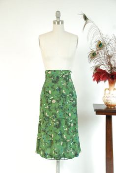 Vintage late 1940s skirt is such a wonderful novelty piece. A cheery print of trees, a happy house, a church with steeple and farmers carts is scattered among the green and black background. Made of a fine silk crepe that is so lovely and soft that I honestly had to test it to be sure it wasnt silk! This elegant piece has just been converted to a skirt, as it could not be restored as a dress. It is styled with a wide early 40s style waistband, dramatic at front and slim at the back. The silk…