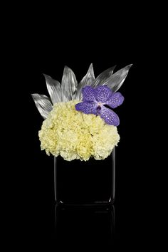 White dianthus , vanda orchid and silver aspidistra leaves on black glass vase Armani/Fiori