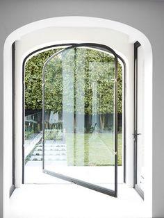 Uma porta de aço e vidro, em arco e pivotante. Diferente, mas bonita. A sensação de quem está do lado de dentro deve ser de que se está lá fora (e vice-versa).