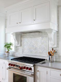 Caesarstone Pebble; Love herringbone/chevron tile within the picture frame molding over the stove