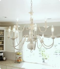 This is what we did in the baby's room, only it is a single, not double chandelier. Brassy to classy white chandelier, spray painted. Spray Painted Chandelier, White Chandelier, Chandelier Lighting, Chandelier Redo, Painting Chandeliers, Plastic Chandelier, Table Lighting, Iron Chandeliers, Paint Brass