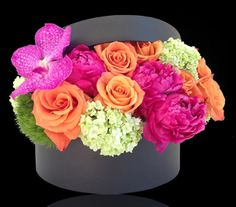 """Stapleton Floral Design - A beautiful bouquet of spring flowers in vibrant hues of magenta, tangerine and green, artistically arranged in a 9""""diameter x 4""""high round box."""