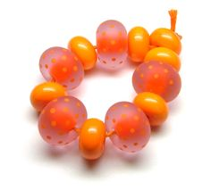 Dark orange, encased in rose pink, decorated with orange polka dots and etched to a velvety finish. Beads by Laura