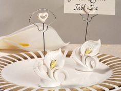 These white resin calla lily place card holders would add a special touch to your elegant affair. After your affair your guests can use these adorable favors in their homes as a photo holder. Calla lily design attached to a wire holder with resin hearts at the top. Each resin place card holder stands 4.5 tall.