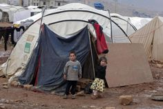 Syrian children stand near their tent at a refugee camp in the eastern Lebanese border town ...