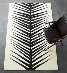 Natural habitat. Ivory wool lays natural base for solid black flora pattern. Bold in size/color/shape, botanical print runs full-length down the center, creating two symmetrical halves. A neutral way to do flora or animal print, this ivory and black rug will be at home in any room. CB2 exclusive.
