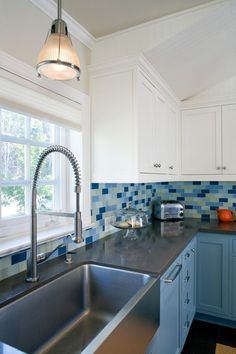 Jeff Troyer Associates selected brilliant blues to create an inviting, soothing color palette that unites the remodeled kitchen, bathroom and laundry room in this home. Updated appliances and fixtures add the perfect finishing features. From the experts at HGTV.com.