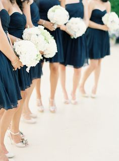a lineup of navy blue bridesmaid dresses and all white bouquets  Photography: Jen Huang Photography - jenhuangphotography.com Floral Design: Fleurs - fleursnyc.com  View entire slideshow: 4th of July Wedding Details on http://www.stylemepretty.com/collection/431/
