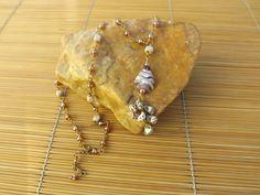 colar ouro velho,feito com miçangas,quadradinhos de madeira,conchinhas do mar e um peixe de murano.