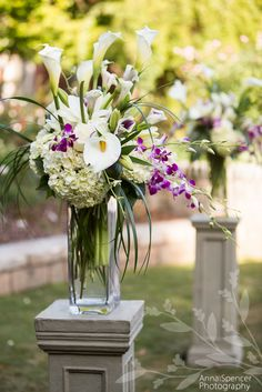 White and purple wedding ceremony flowers by Fuji Floral Designs.