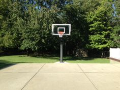 The trees offer a scenic backdrop for this Pro Dunk Gold Basketball system. The play area is made of concrete, borrowed from the 2 car driveway.