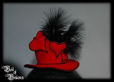 Mini queen-of-hearts hat in velvet, decorated with hearts and black feathers. £25
