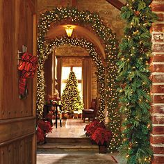 Christmas decor- arched walkway decorated with greenery & white lights.  So pretty!
