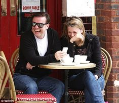 Ricky Gervais and his partner Jane Fallon laugh out loud over some phone humor in London, England