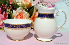 Royal Grafton Viceroy vintage fine bone china milk jug and sugar bowl. c.1970s  Extremely fine quality china and decoration. A broad gold band at the foot, a clotted cream body and a cobalt blue band near the rim. The blue is overlaid with a delicate gold classical design with an egg and dart lower band and a thick gold upper band. The milk jug handle is finely detailed with gold. Half pint milk jug - wear to the gold gilding on the rim otherwise in excellent condition. Sugar Bowl 11cm wide…