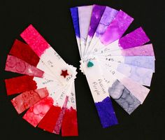 """My red and purple alcohol ink swatches I made to more easily see what colors look good together. I cut alcohol ink paper into 1"""" x 4.25"""", punched holes in one end for a brad, and daubed alcohol ink on the other end. I also included the name or number of the ink."""
